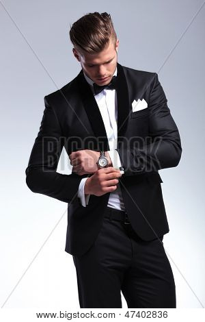 elegant young fashion man in tuxedo looking at his cufflinks while fixing them. on gray background