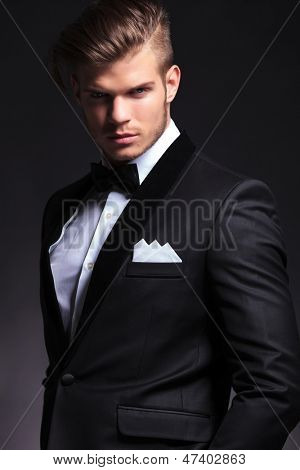 portrait of an elegant young fashion man in tuxedo looking at the camera.on black background