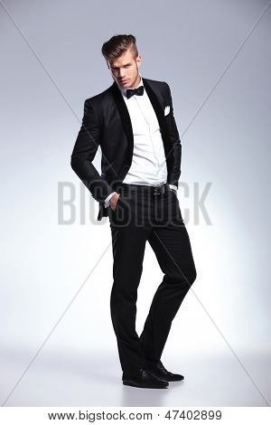 full length portrait of an elegant young fashion man in an unbuttoned tuxedo looking at the camera while holding his hands in his pockets. on gray background