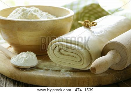 homemade puff pastry and flour on a wooden board