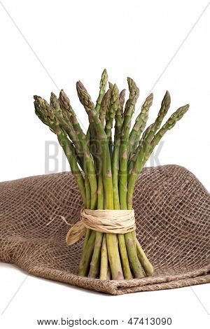 A bundle of asparagus tied with raffia, standing on sackcloth, over white background