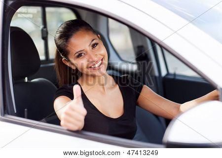 beautiful businesswoman giving thumb up inside her new car