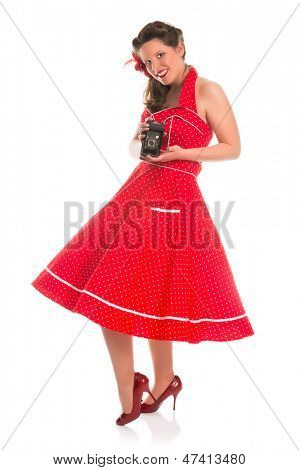 Smiling pin-up girl in fifties polka dot dress taking photos with a vintage camera
