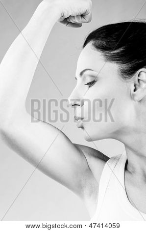 sporty woman is kissing her biceps muscle on grey background