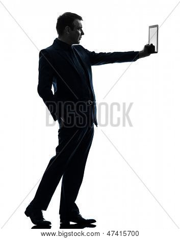one caucasian business man holding digital tablet   in silhouette on white background