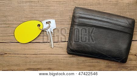 wallet and key with blank label on wood background