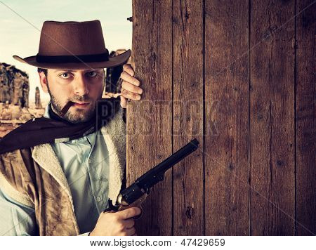 Bad Gunman Indicates With The Gun A Wooden Plank