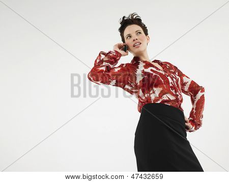 Young woman using cellphone against white background