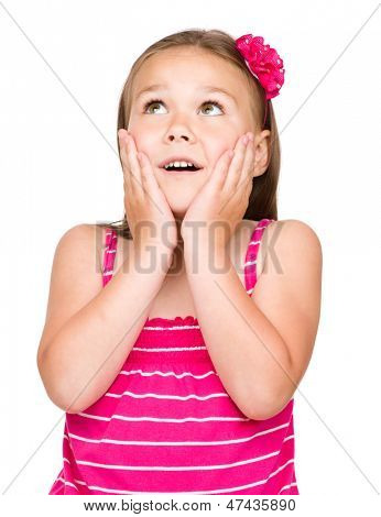 Little girl is holding her face in astonishment and looking up, isolated over white
