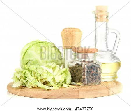 Green cabbage, oil, spices on cutting board, isolated on white