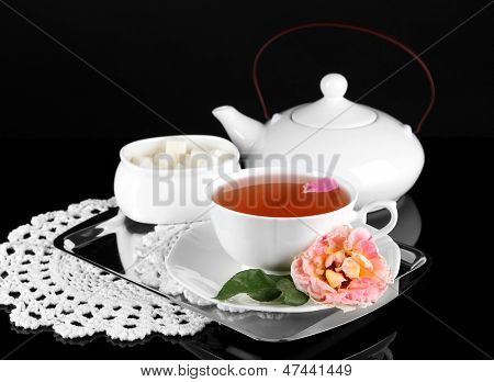 Kettle and cup of tea from tea rose on metallic tray on napkin black background