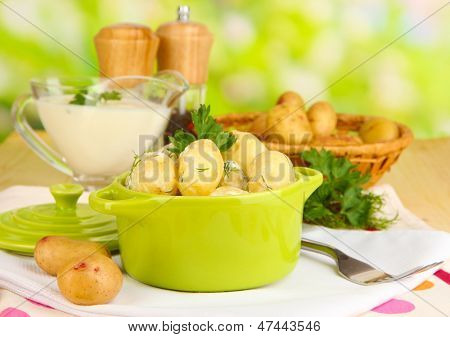 Tender young potatoes with sour cream and herbs in pan on wooden table on natural background