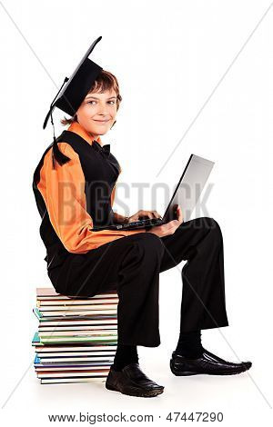 Happy schoolboy in academic hat sitting on a stack of books and holding a laptop. Isolated over white.