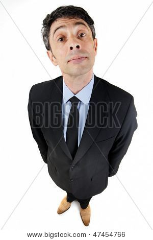 Fun high angle full length portrait of a haughty businessman with a supercilious expression looking up at the camera isolated on white