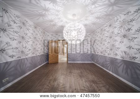 Spacious room with unusual chandelier and opened door in new apartment.