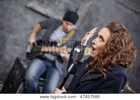 Female lead vocalist and guitarist in studio during shooting videp clip, turned frame