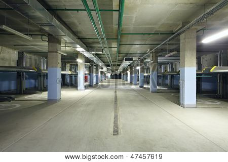 Large indoor two-level parking with electrolifts for many cars.
