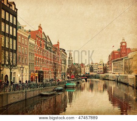 The Singel is one of the numerous canals in Amsterdam, Netherlands . In the background Munttoren . Photo in retro style. Paper texture.