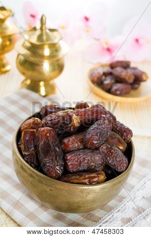 Dried date palm fruits or kurma, ramadan food which eaten in fasting month. Pile of fresh dried date fruits in golden metal bowl.
