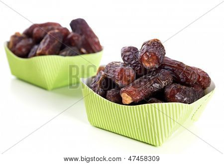 Dried date palm fruits or kurma, ramadan food which eaten in fasting month. Pile of fresh dried date fruits ready to eat in paper boxes.