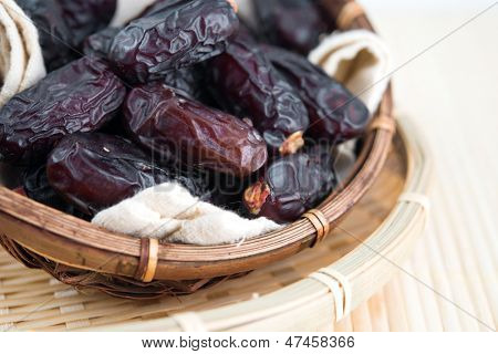 Dried date palm fruits or kurma, ramadan food which eaten in fasting month. Pile of fresh dried date fruits in bamboo basket.
