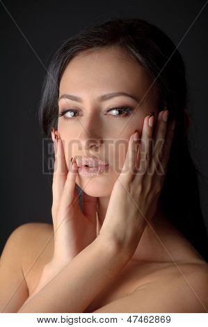 Portrait Of Young Attractive Brunnete Woman Holding Her Face In Her Hands With Sugar On Her Lips