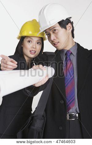 Studio shot of businesspeople wearing hard hats