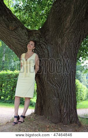 Outdoor shot of attractive slim happy smiling young woman in yellow dress under the tree