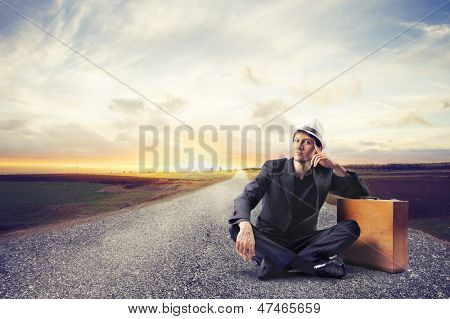 young man sitting on the road waiting with suitcase