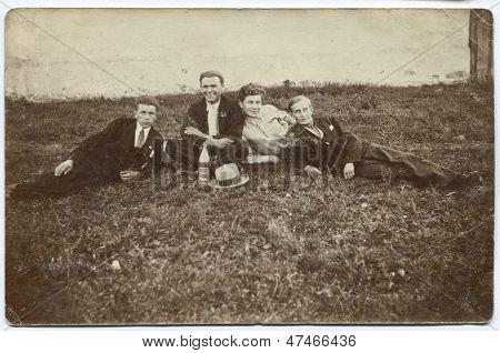 CZESTOCHOWA, POLAND, CIRCA 1934- vintage photo of four men picnicking with a bottle of vodka, Czestochowa, Poland, circa 1934