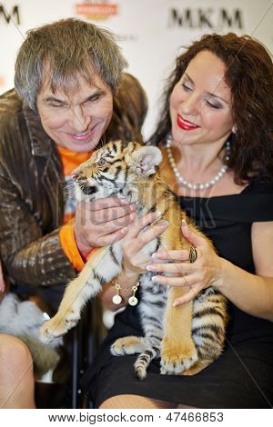 MOSCOW - OCT 22: Circus actress, animal trainer Karina Bagdasarova with tiger cub and soviet and russian musician and producer Bari Alibasov at Phoney New Year celebration, Oct 22 2012, Moscow Russia.