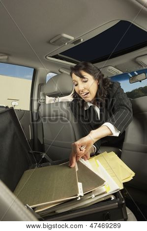 Businesswoman getting files out of the backseat