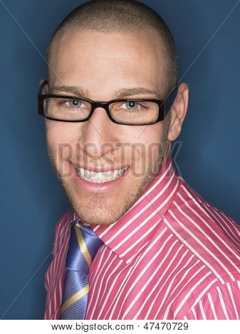 Portrait of a smiling bald man in glasses against blue background