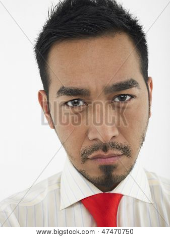 Closeup portrait of a young man frowning against white background
