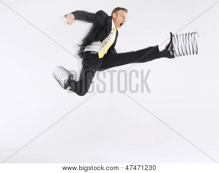 Full length of a businessman jumping with springs on feet against white background