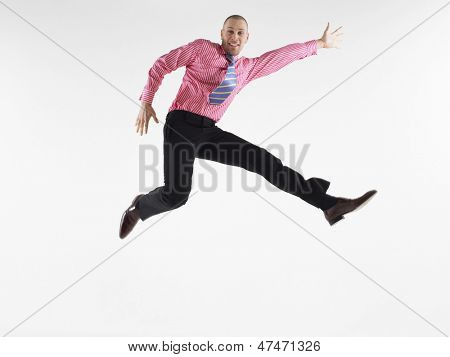 Full length portrait of a bald businessman jumping against white background