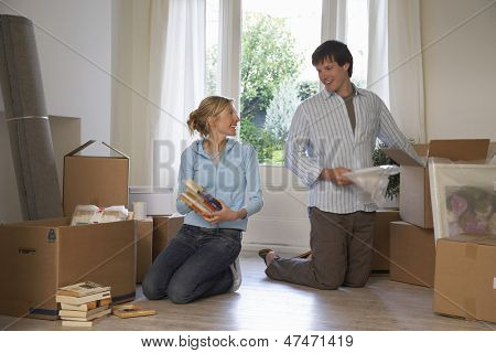 Young couple unpacking boxes at their new home
