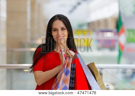 Young Woman Shopping in Mal Holding paper Bags
