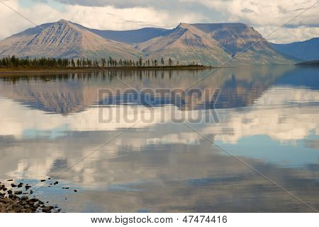 Lake Lama And Reflected In The Water Clouds And Mountains Of The Peninsula Of The Stone.