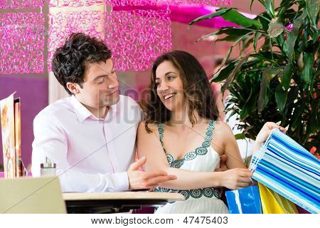 Young Couple in a Cafe or Ice cream parlor, she showing something in a bag