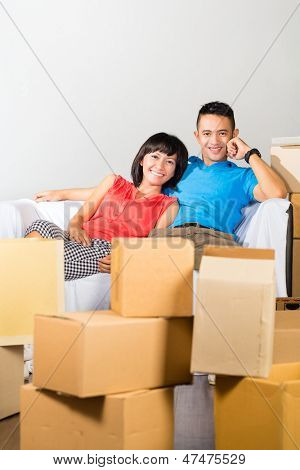 Real estate market - Young Indonesian couple moving in a home or apartment, they are sitting on the sofa and having a break