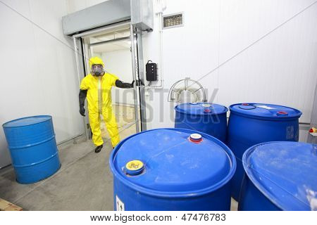 technician in protective uniform checking barrels with toxic substance in plant