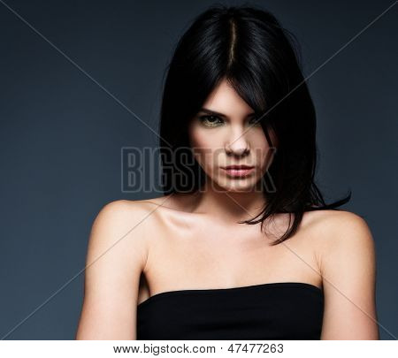 Young beautiful strict brunette woman isolated on grey background