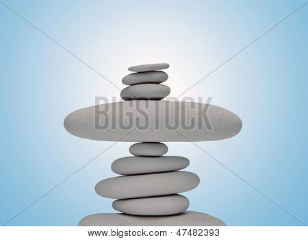 Balancing smooth stones against blue graduated background.