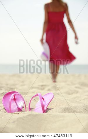 Girl With Slippers On A Beach