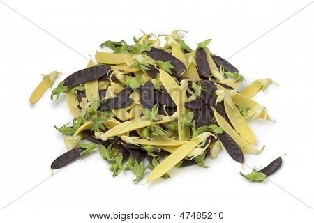 Heap of yellow and purple snow peas on white background