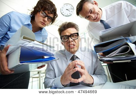 Pleading accountant looking at camera being surrounded by his partners holding huge piles of documents