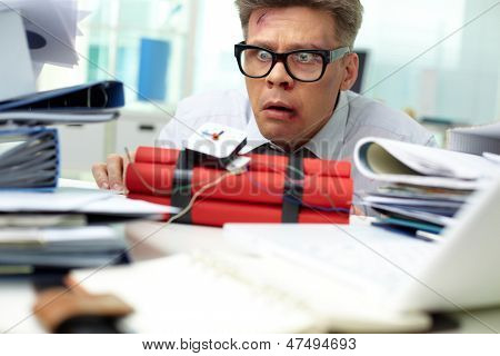 Terrified businessman looking at dynamite