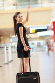 stock photo of bye  - cheerful businesswoman waving goodbye at international airport - JPG
