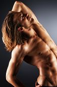 stock photo of striptease  - Sexual muscular nude man posing over dark background - JPG